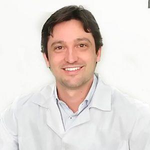 Dr. André Schmidt, tem os cabelos pretos e curtos, ele está sorrindo na foto e tem dentes bastante brancos. Está vestindo uma camisa branca, com um jaleco branco por cima.