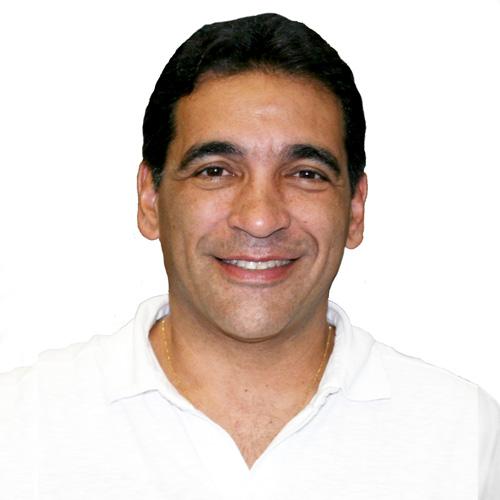 Dr. Cleiton Piotto Assunção tem os cabelos curtos, da cor preta, ele está sorrindo, então os olhos estão levemente apertados. usa uma camiseta polo branca e uma correntinha de ouro.