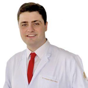 Dr. Leonardo Calixto Lemos - Ortodontia - ele tem cabelos pretos, rosto arredondado, usa uma camisa branca, gravata vermelha e usa jaleco branco.