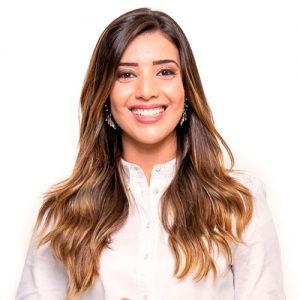 Luna Vinhas Bueno - Fisioterapeuta - ela tem longos cabelos cor de mel, levemente ondulados, ela está sorrindo e usa um jaleco branco.
