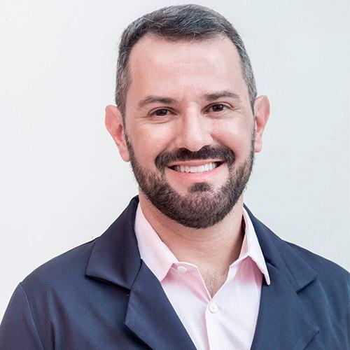 Jean Pierre Beltrão Bedouch - Dentista - está usando uma camisa rosa clarinho, com um jaleco cinza escuro por cima. Ele tem cabelos levemente grisalhos, barba e bigode.