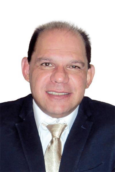 Dr. Jorge Luiz de Mello - Psiquiatra, ele tem cabelos pretos, pele clara e veste um terno escuro, com camisa branca e gravata dourada.