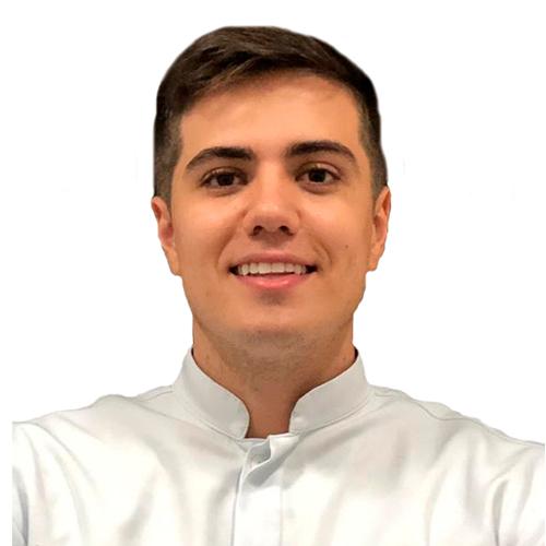 Dr. Matheus Calixto - Dentista d ecabelos pretos, curtos, está sorrindo na foto. Ele usa um jaleco branco.
